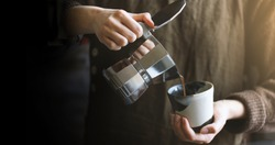 Barista pouring coffee from moka pot coffee maker to the small coffee cup . Professional coffee brewing. Blur background.