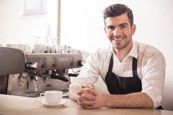 Barista prepares cappuccino in his coffee shop.