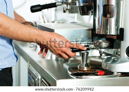 Barista prepares cappuccino in his coffee shop; close-up - stock photo