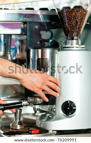 Barista prepares cappuccino in his coffee shop; close-up