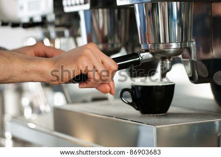Barista prepares cappuccino in his coffeeshop; close-up - stock photo