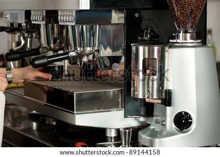 Barista prepares espresso in his coffee shop; close-up