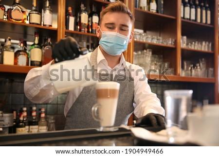 Barista preparing coffee at counter in restaurant. Catering during coronavirus quarantine