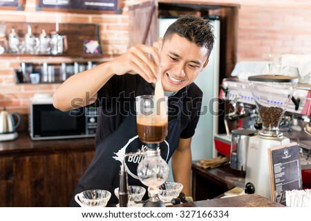 Barista preparing drip coffee in Asian coffee shop using professional machine parts