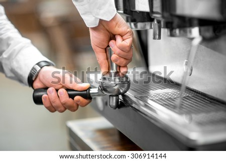 Barista pressing coffee in the coffee machine holder. Close up view focused on hands