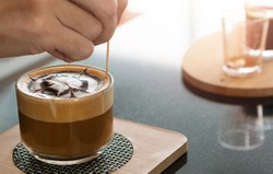 Barista's hands holding and pouring chocolate for prepare cup of coffee, latte art. Barista making latte or cappuccino coffee in cafe. Drawing on latte or cappuccino. Coffee latte art made by barista.