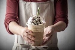 barista serving coffee frappe in plastic cup