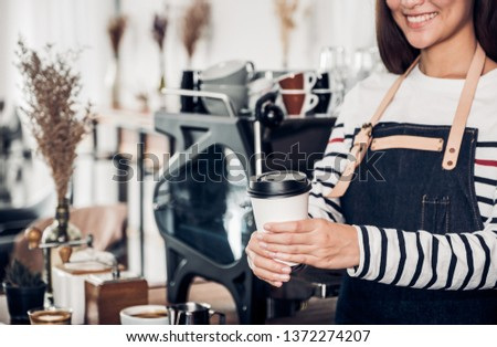 Barista serving take awary coffee cup at cafe.Asian female barista wear jean apron holding coffee served to customer with smiling face at bar counter, restaurant service concept.waitress working
