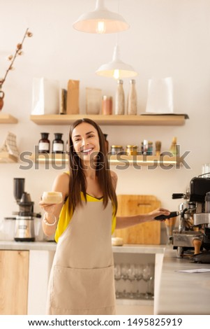 Barista smiling. Pleasant female barista smiling while talking to customer and making coffee