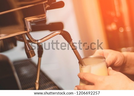 Barista steaming milk for hot cappuccino with machine #1206692257