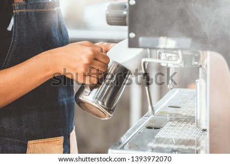 Barista steaming milk in the pitcher with coffee machine, Asian barista making hot coffee