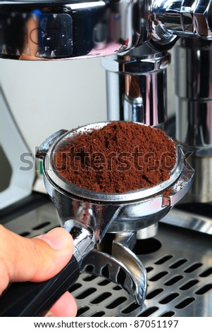 Barista  take coffee grind in group, prepare to brewing espresso shot.