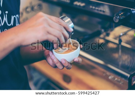 Barista using coffee machine preparing fresh coffee or latte art and pouring into white cup at coffee shop and restaurant, bar or pub #599425427