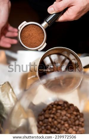 Barista with tamper and piston/portafilter making espresso.