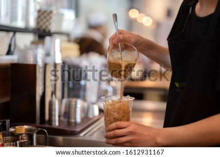Barista Woman barista pouring coffee into takeaway glass in the coffee shop.