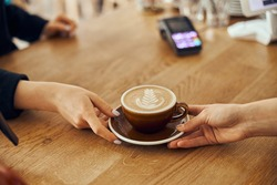 Barista woman giving order to client at the trendy coffee shop. Coffee cup with latte art