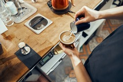 Barista woman making cappuccino, female preparing coffee drink. Coffee cup with latte art