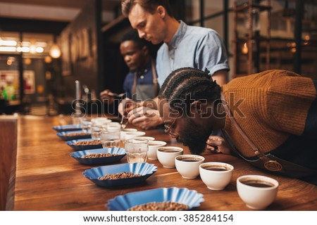 Baristas training with variety of coffee beans in modern roaster
