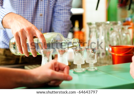 Barkeeper pouring hard liquor into glasses standing on the bar