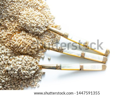 Barley , pearl barley and Job's tears. Placed on brass spoon. White background.