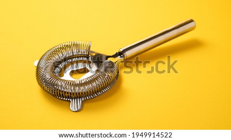 Barman equipment. Sieve for cocktails. Cocktail strainer on yellow background. Bartender strainer. Bartender tools Stock photo ©