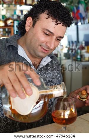 Barman fills glass. Smiling man against shelves with bottles.