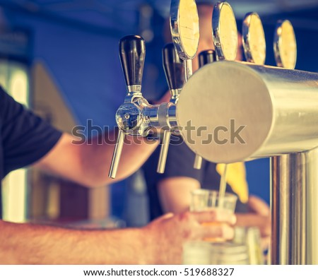 Barman hand at beer tap pouring a drought lager beer serving in a restaurant or pub.Vintage look