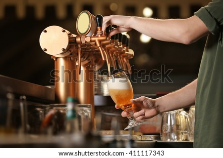 Barman hands pouring a lager beer in a glass. #411117343