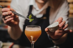 Barman is decorating cocktail with rocket no face