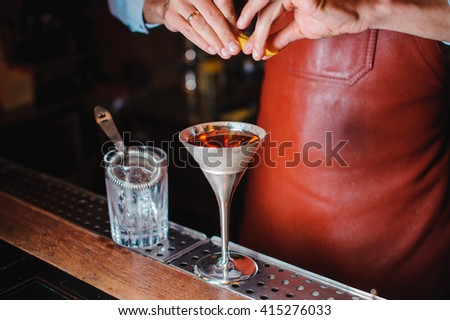Barman is finishing up cocktail with lemon no face #415276033