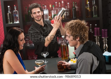 Barman making cocktail for young couple at the bar