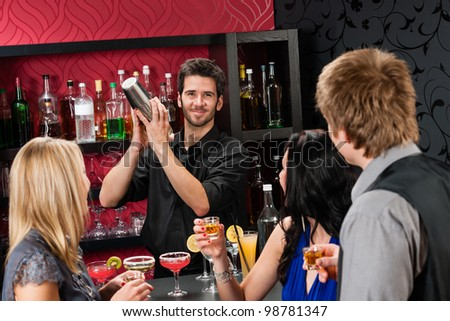 Barman making cocktail for young friends at the bar #98781347