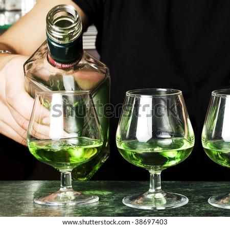 Barman making cocktail.Several glasses of absinthe.