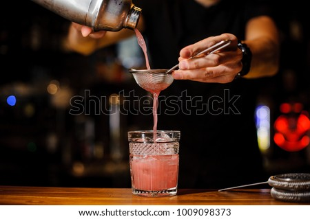 barman poured an alcoholic cocktail of pink color from the shaker through a strainer into a crystal glass using bar equipment - Shutterstock ID 1009098373