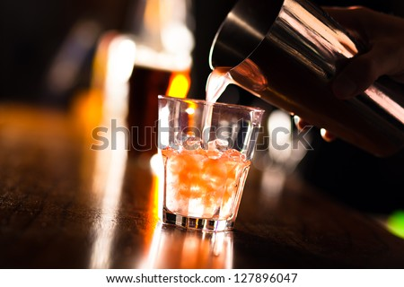Barman pouring a cocktail into a glass