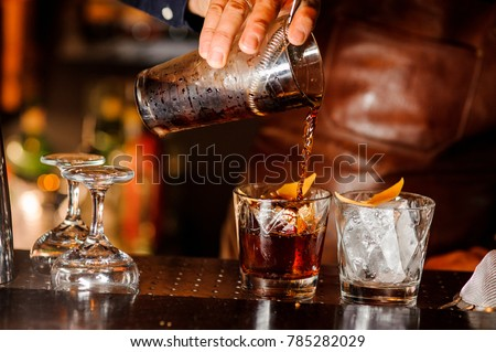 Barman pouring fresh alcoholic drink into the glasses with ice cubes on the bar counter