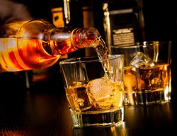 barman pouring whiskey in front of whiskey glass and bottles on wood table