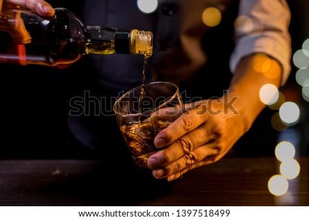 Barman pouring whiskey whiskey glass.. #1397518499