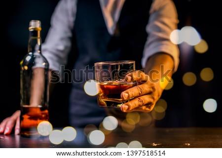 Barman pouring whiskey whiskey glass.. #1397518514