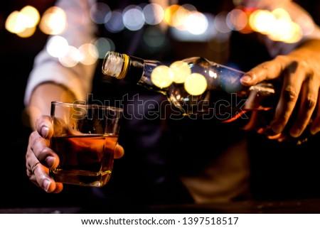 Barman pouring whiskey whiskey glass.. #1397518517