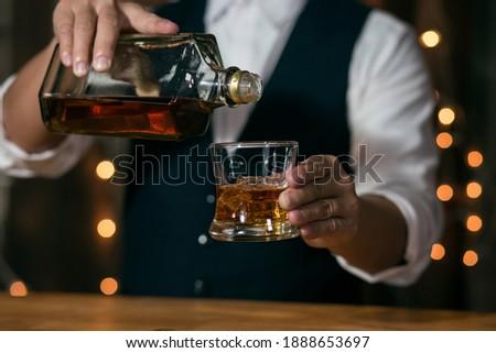Barman pouring whiskey whiskey glass beautiful night ストックフォト ©
