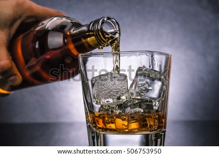 barman pouring whiskey whiskey with ice cubes in glass on black background, cold atmosphere, time of relax with whisky #506753950