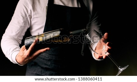 barman puring red wine. dark background #1388060411