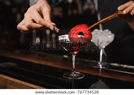 Barman`s hands decorating a cocktail glass with fresh red alcoholic drink with a slice of beet