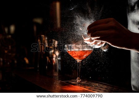 Barman`s hands sprinkling the juice into the cocktail glass filled with alcoholic drink on the dark background #774009790