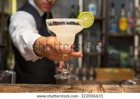 Barman serving margarita cocktail
