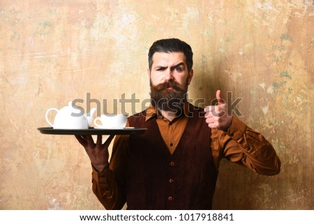 Barman with strict face serves tea or coffee showing thumbs up. Man with beard and mustache holds tea on beige wall background. Waiter with white tea cup and pot on tray. Service and catering concept #1017918841