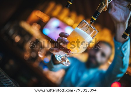 Barmen or brewer filling glass with beer. Barmen is pouring lager beer to glass from  beer taps. Bar or night club interior #793813894