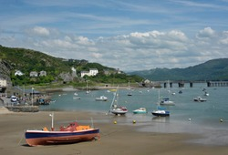 Barmouth town and harbour with landmark Barmouth railway viaduct over the estuary of the river Mawddach and Cardigan Bay, the marina and quay in Gwynedd, North Wales, UK.
