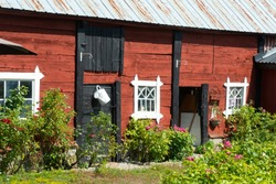 Barn building on an old farm on the Swedish Baltic Sea island in summer. Brilliant, rich colors, with the characteristic Swedish copper red as an eye-catcher